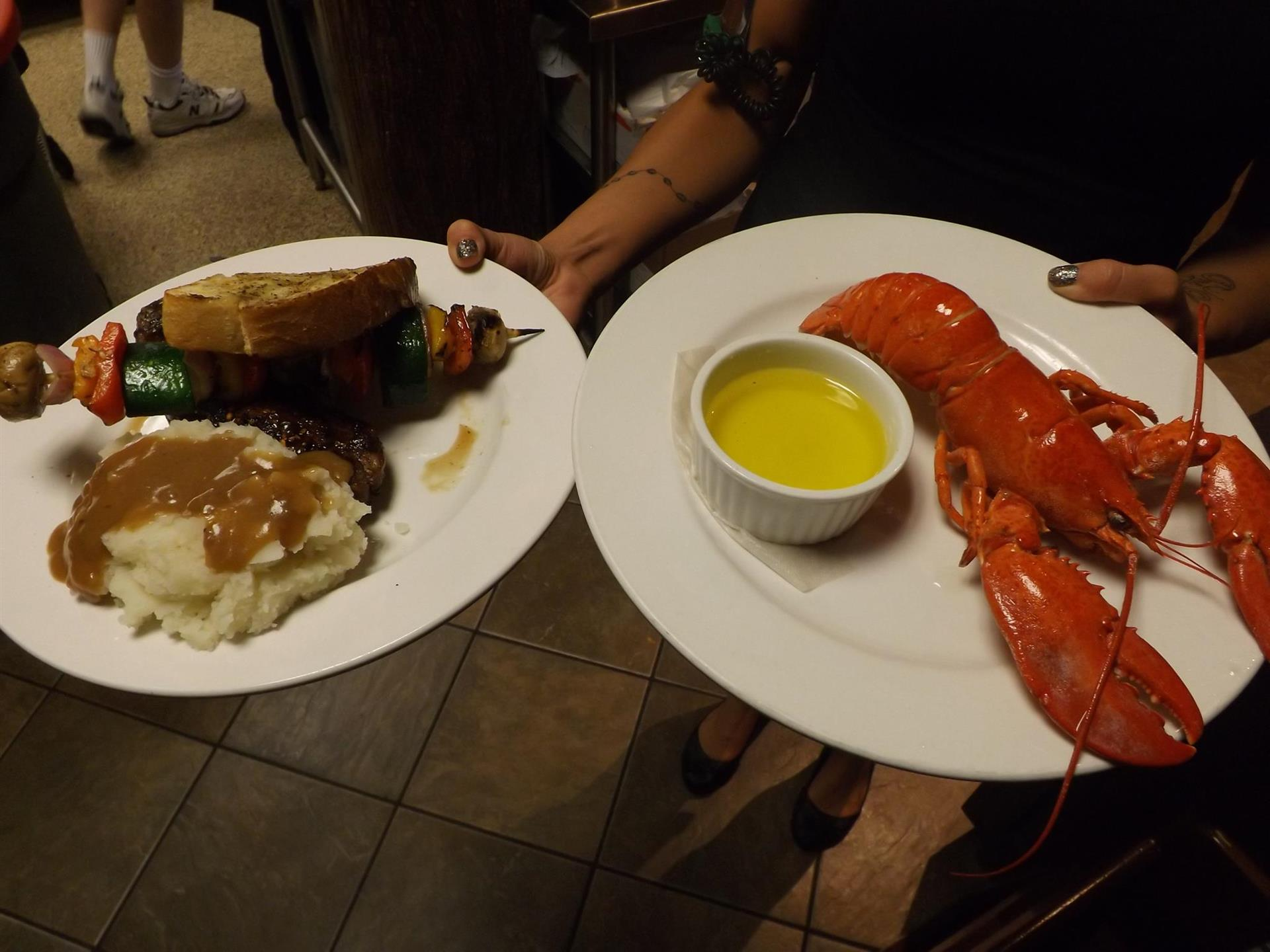 a person holding two white plates. one with mash potaatos and gravy and a shish kebab with a slice of bread. Another plate with a small cup of butter and a lobster