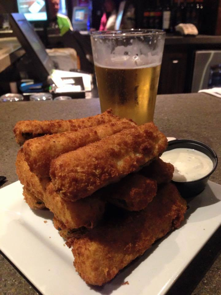 stack of mozzerella sticks with a side of white sauce and a cup of beer