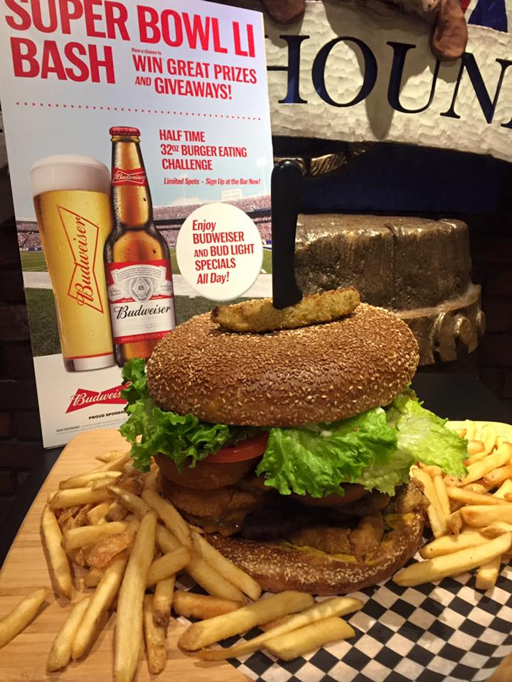 a large burger with lettuce and tomato and a side of fries