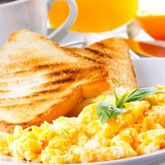 Scrambled eggs with a side of toast, coffee, and orange juice