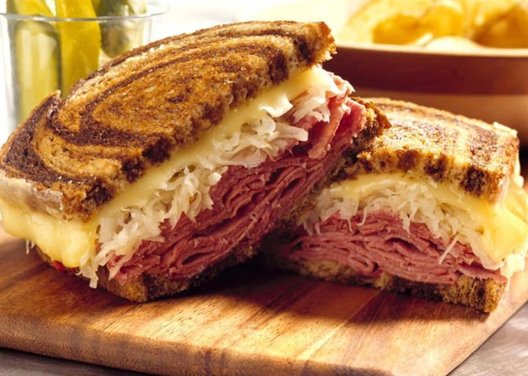 A corned beef and cabbage sandwich on marble rye bread