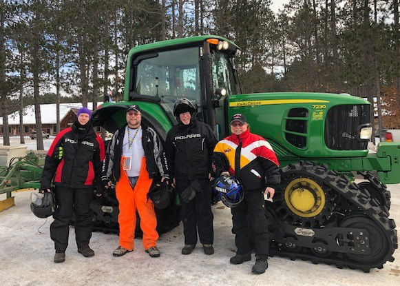 4 Men in snow gear smiling in front of a large tracker