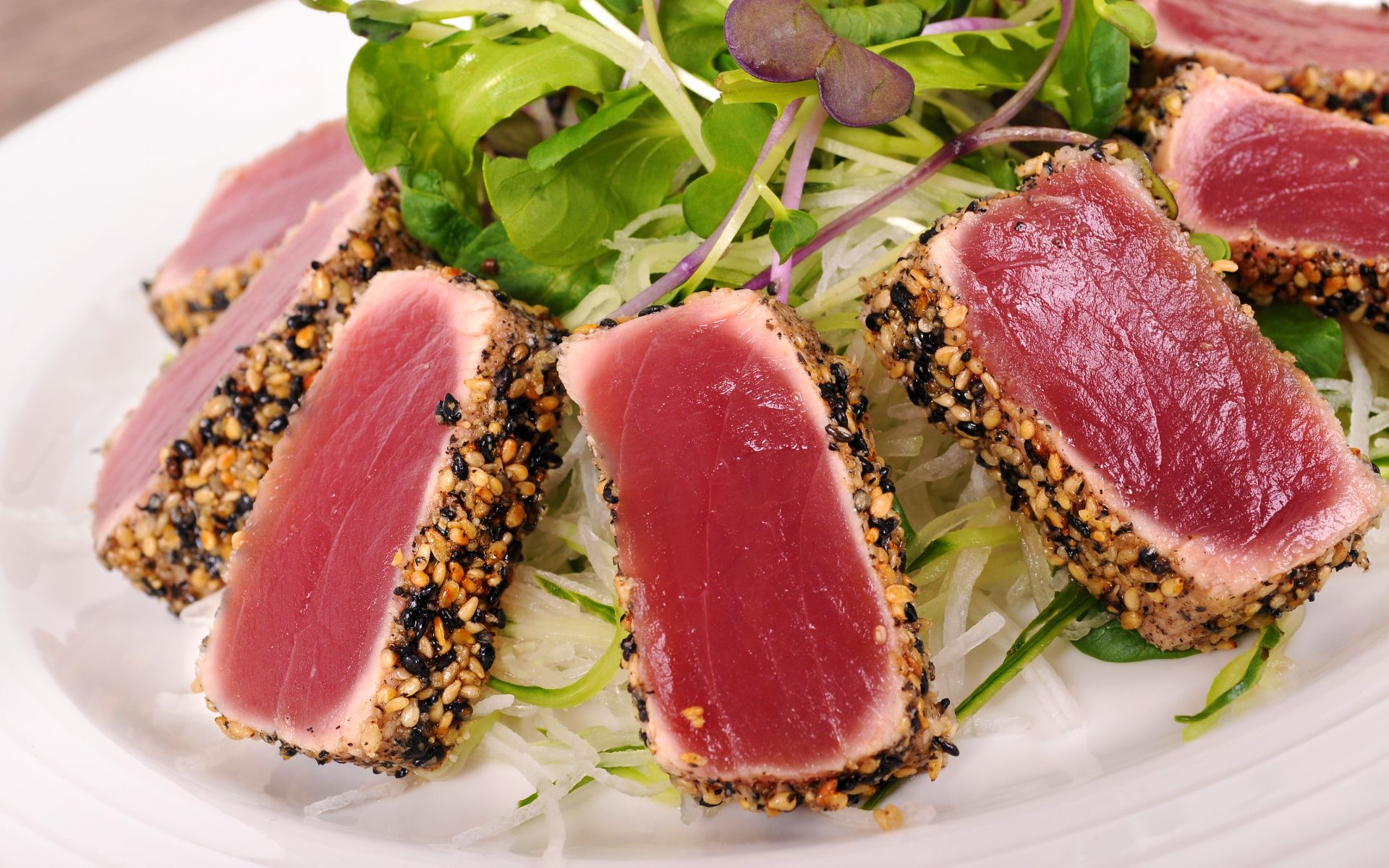 sesame tuna tar tar on a bed of greens