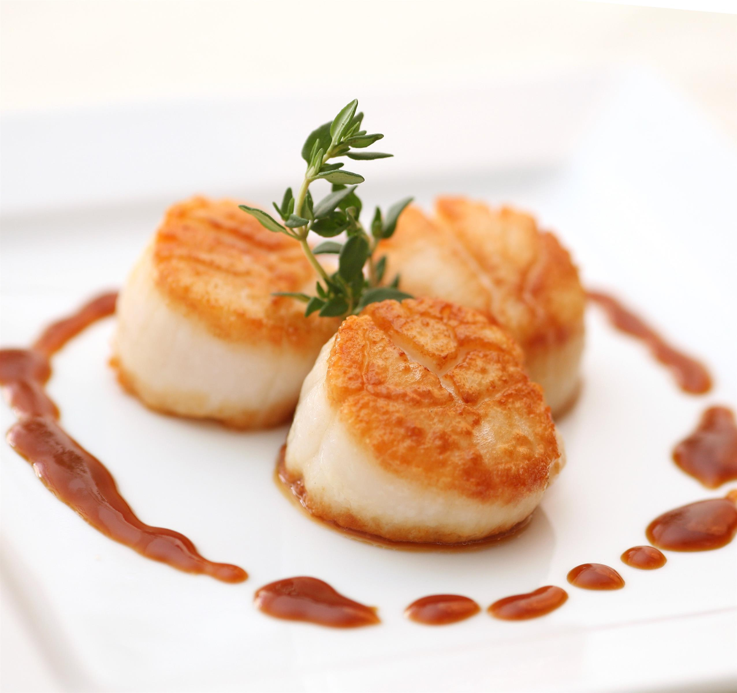 seared sea scallops with thyme and a sauce on the side