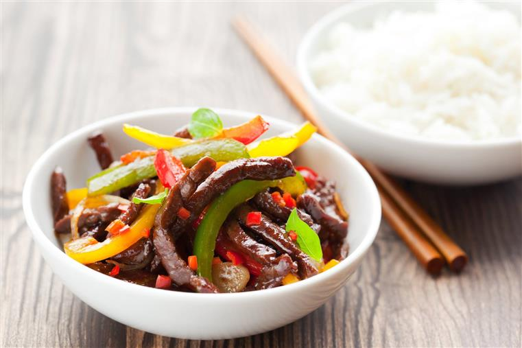 bowl of steak and bell peppers, bowl of white rice, pair of chopsticks all on a table