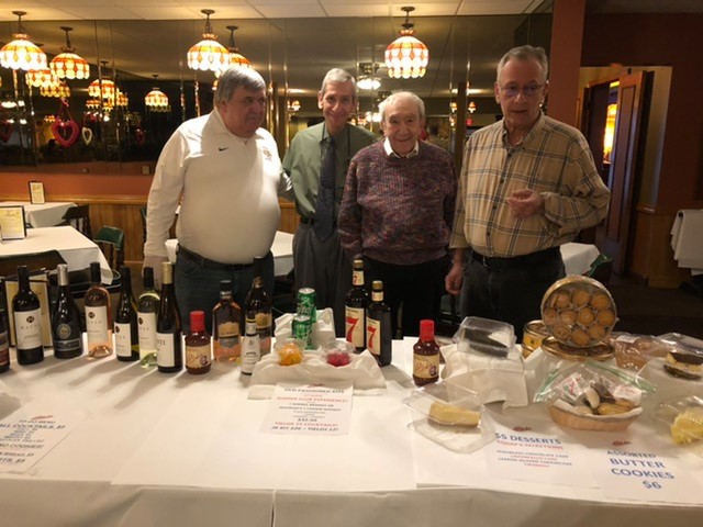 men at display table with liquor display