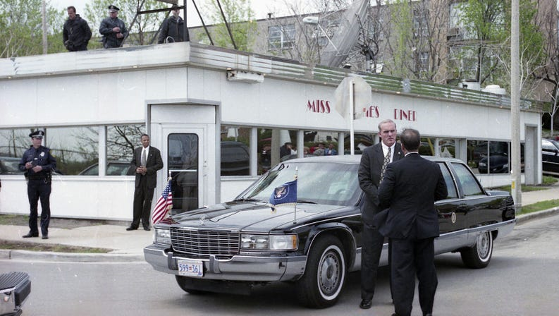 outside of diner surrounded by a limo and men in suits