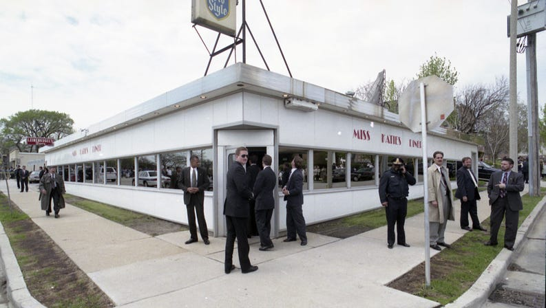 outside of diner with several people in suits