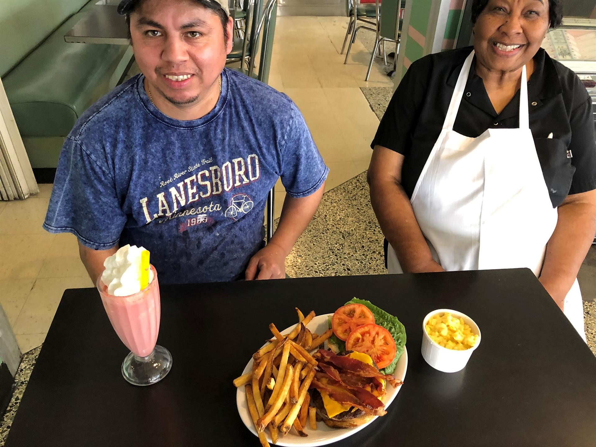 2 employees with a burger, fries and shake