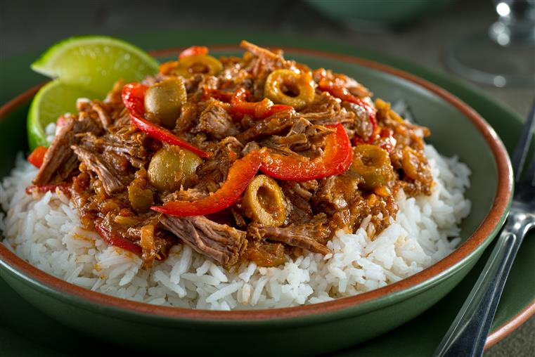 bowl of white rice, topped with shredded beef, roasted peppers, and sliced green olives