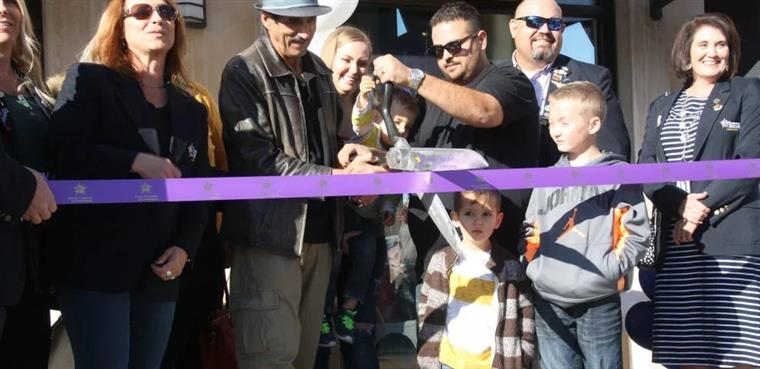 The grand opening of Santorini's Greek Grill with the owner cutting the ribbon