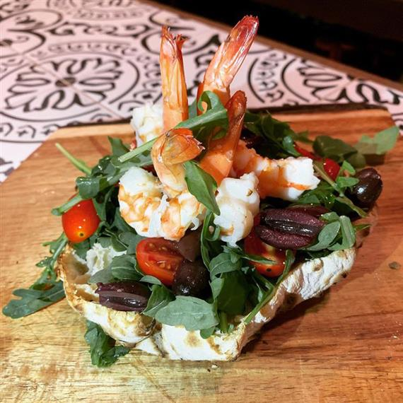 A shrimp and arugula salad topped with cherry tomatoes on bread