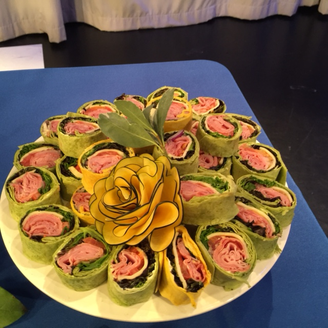 handheld ham, cheese and vegetables wraps on a tray