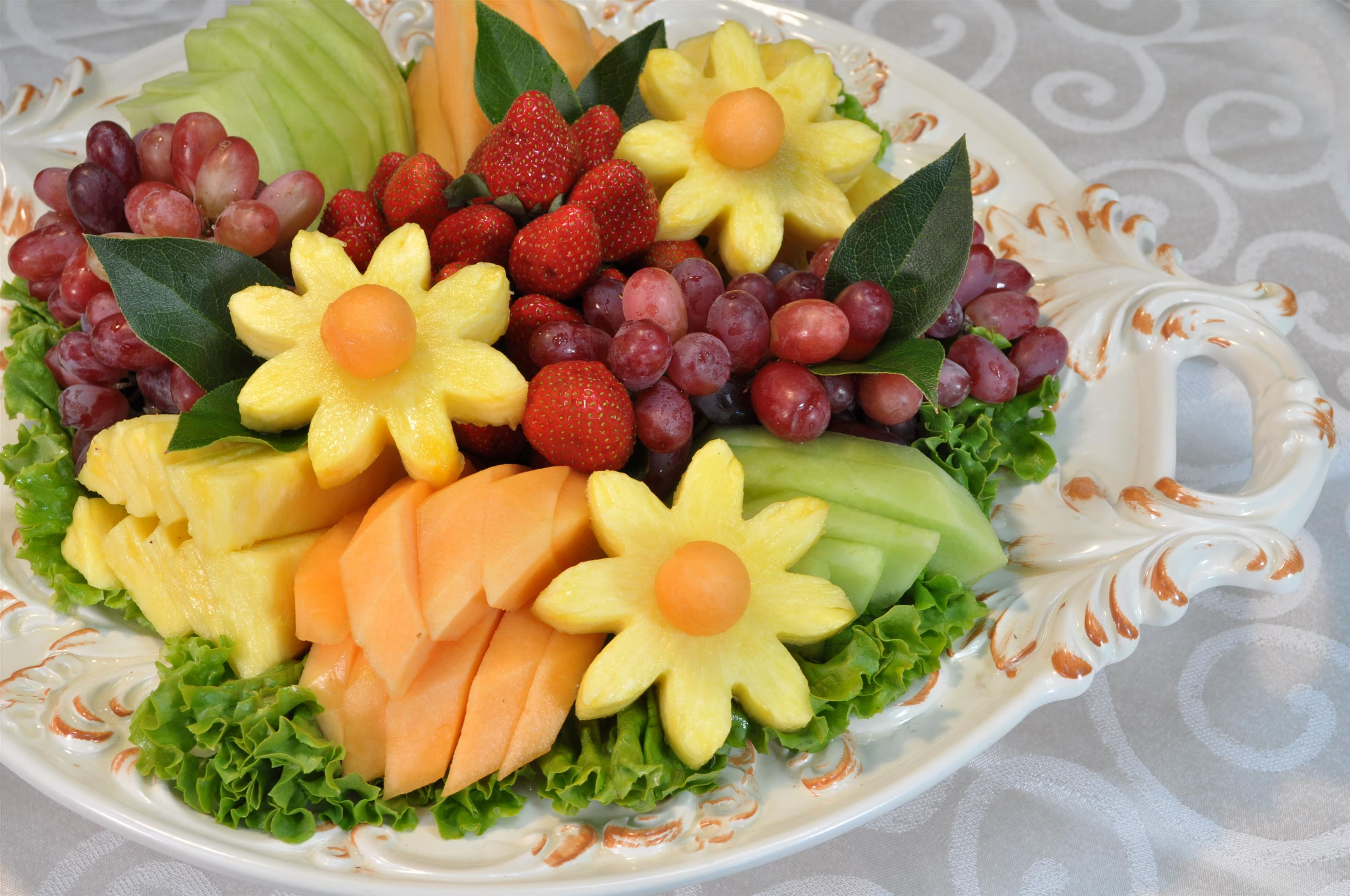 assorted fruit platter with some shaped like flowers
