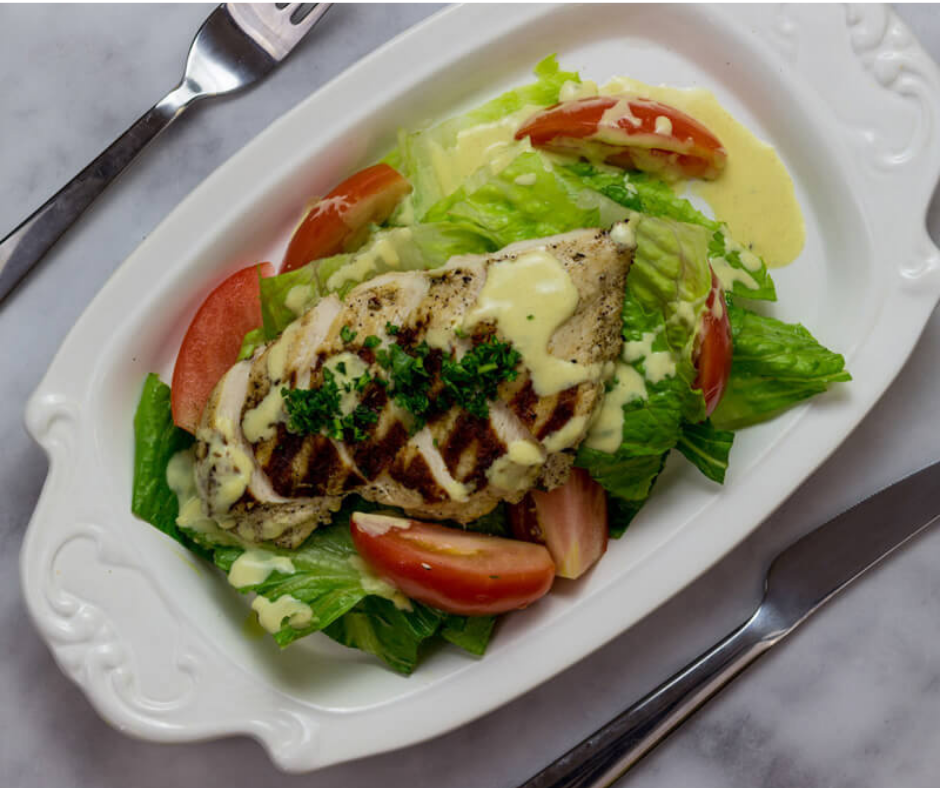 salad topped with grilled chicken and tomatoes