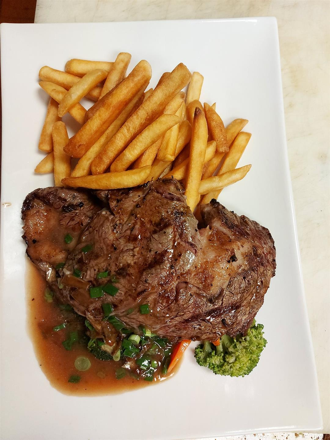 grilled steak with a side of french fries