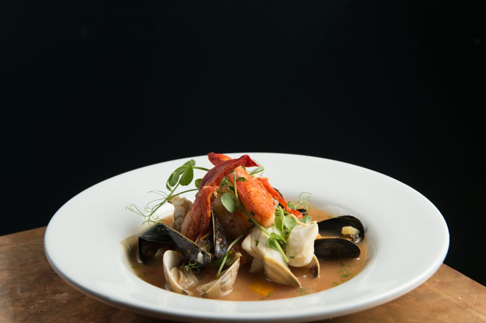 lobster claw over a bed of mussels and clams in a broth