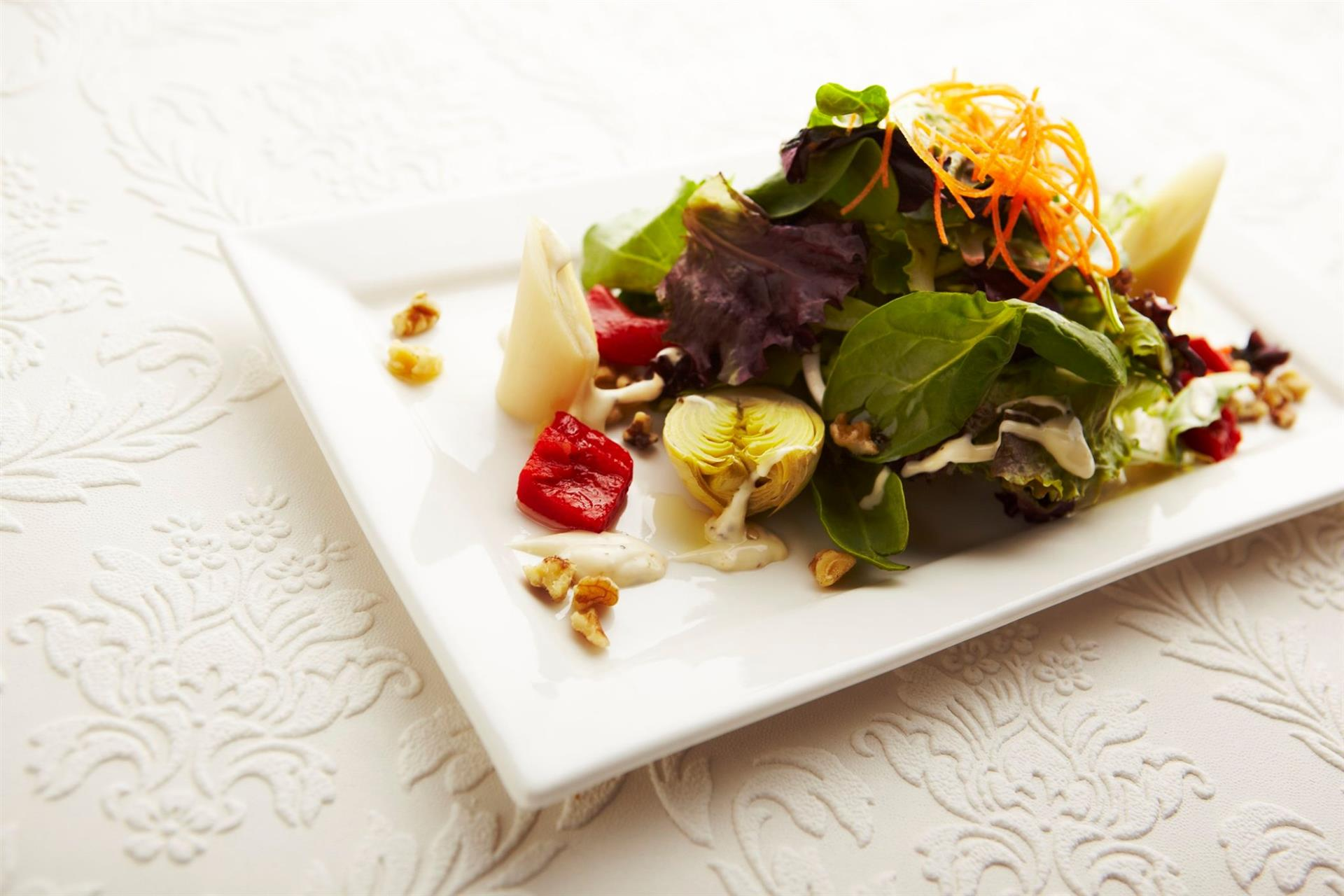 salad topped with shaved carrots and dressing
