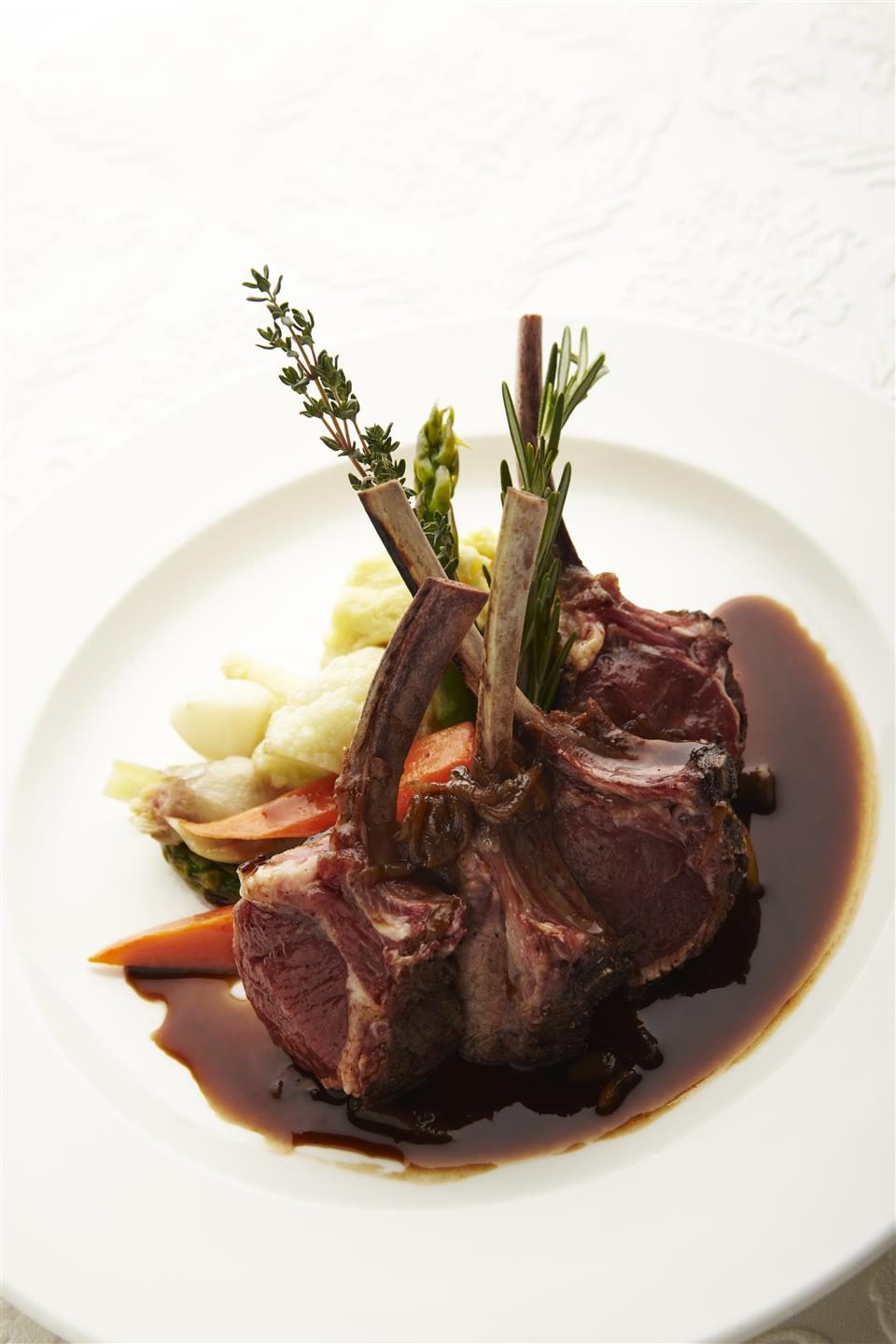 lamb chops topped with sauce and garnish