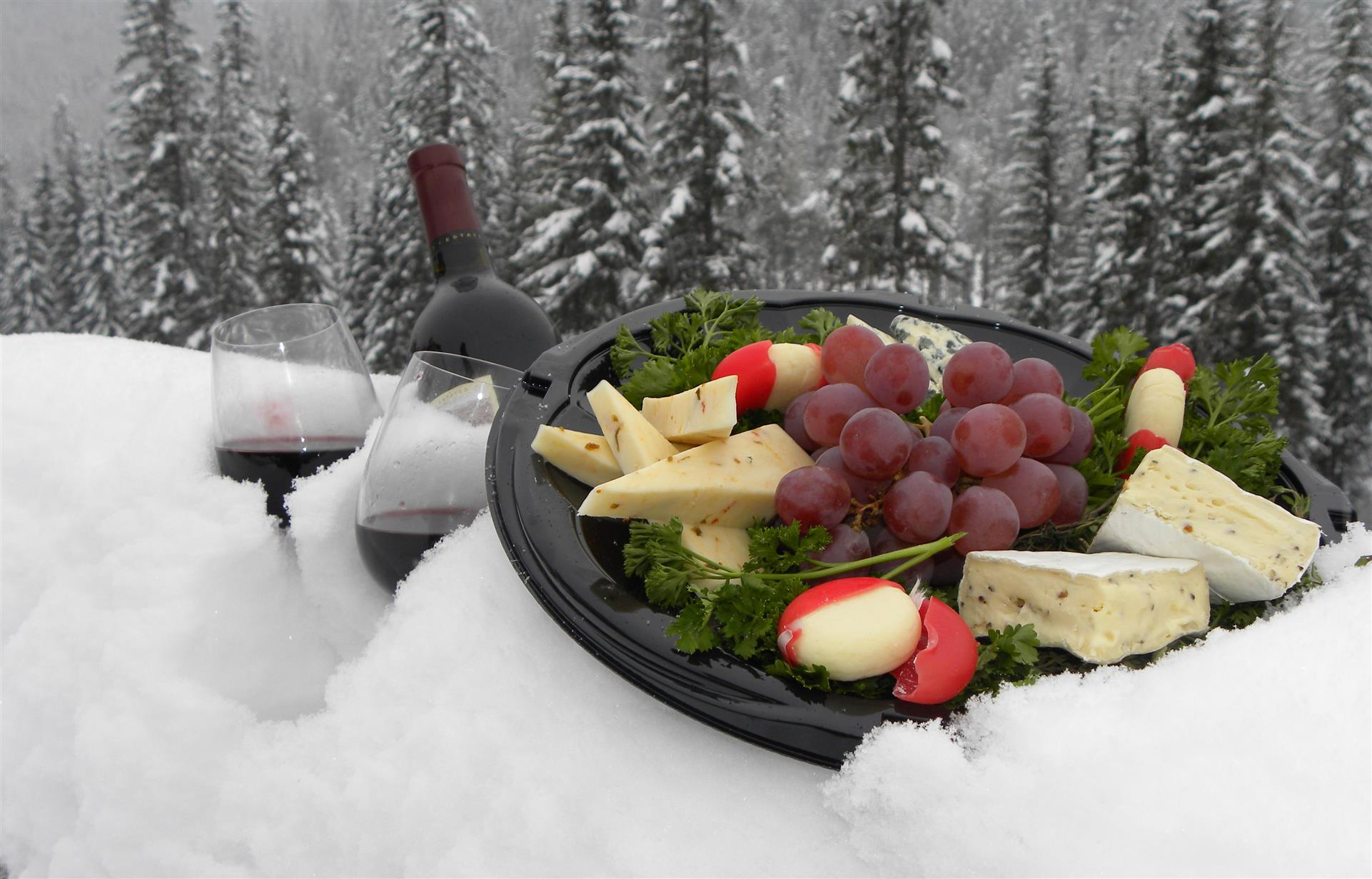 platter with grapes, cheese, and wine in the snow