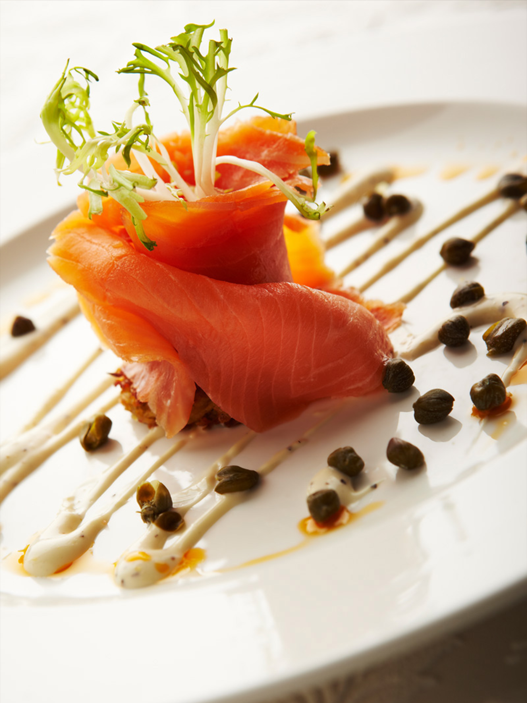 raw salmon topped with garnish and capers