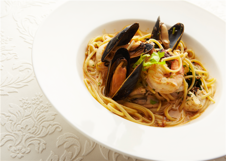 Seafood Linguine with shrimp, calamari, salmon, and mussels in a white wine tomato broth