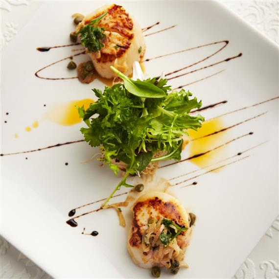 grilled scallops on a plate with garnish
