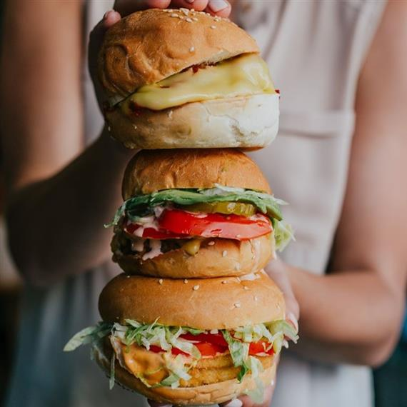 woman holding a stack of vegan burgers and sandwiches with lots of toppings