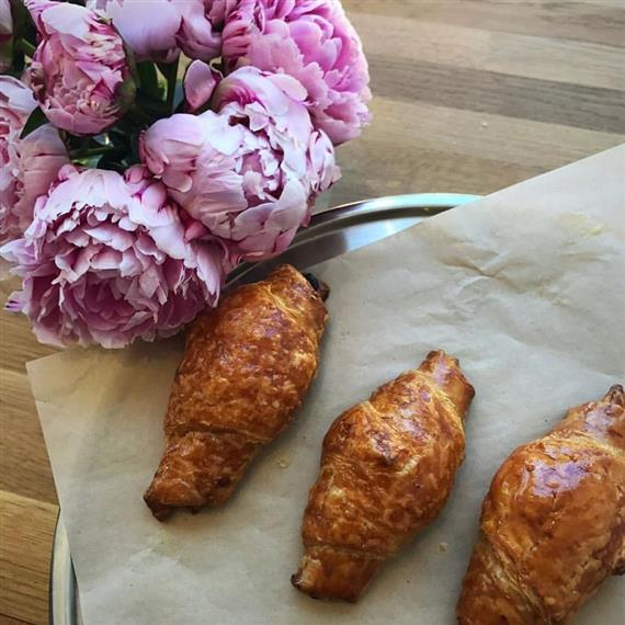 homemade vegan croissants on parchment paper next to fresh flowers
