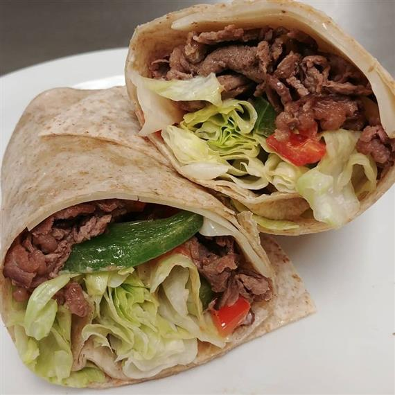 whole wheat wrap with grilled steak, lettuce, bell peppers, and tomato