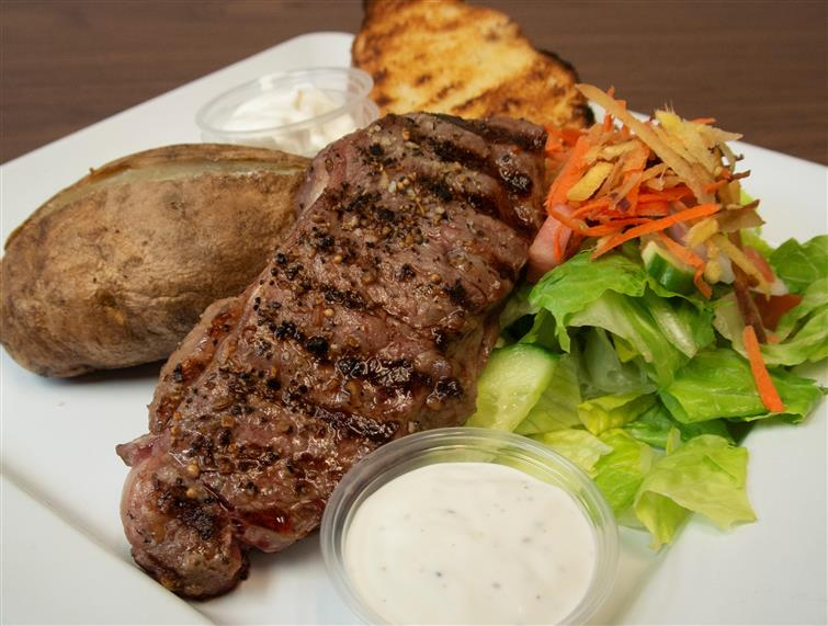 steak with a baked potato and a side salad