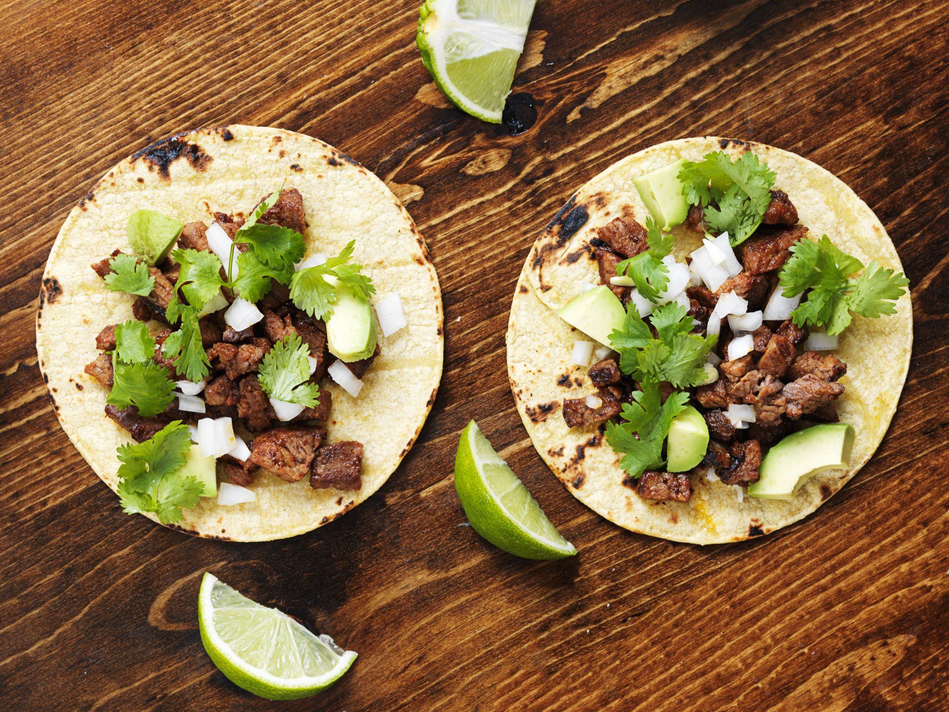 two steak street style tacos with white onions and cilantro in soft corn tortillas and lime wedges on the side