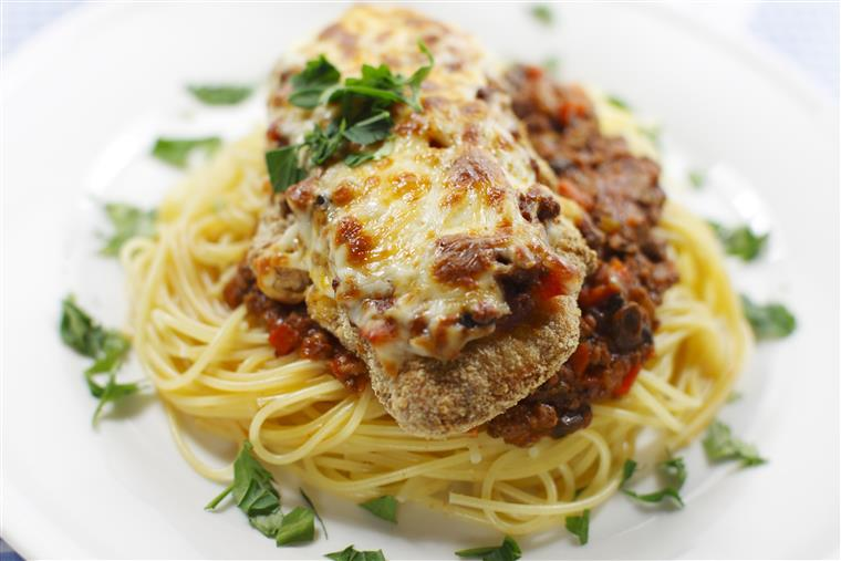 chicken parmesan with sauce and melted cheese on top of spaghetti