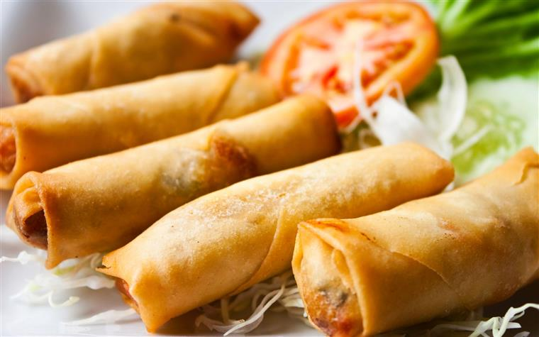 spring rolls on a plate with greens and tomato