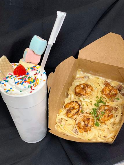 milkshake with sprinkles, wafers, and and marshmellows with takeout box of shrimp fetuccini alfredo