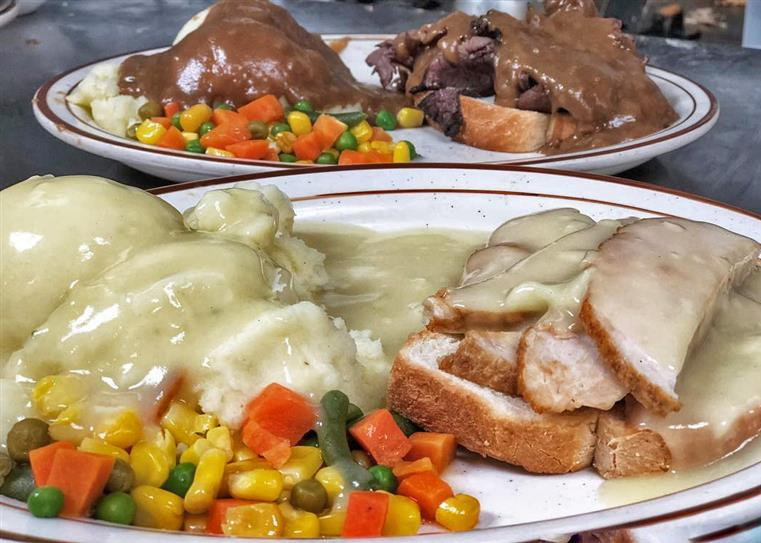 Mashed potatoes and turkey topped with gravy. Mixed Vegetables on the side