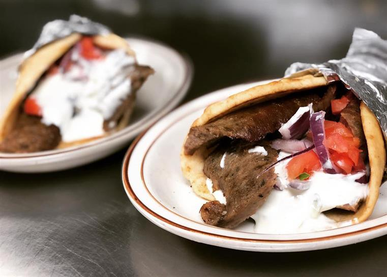 A gyro topped with onion, tomato, and tzatziki sauce.
