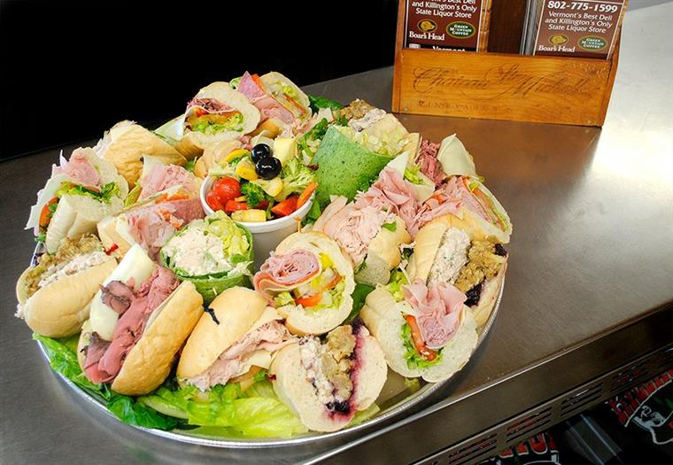 platter of assorted deli sandiwches and wraps next to menu holder on a countertop