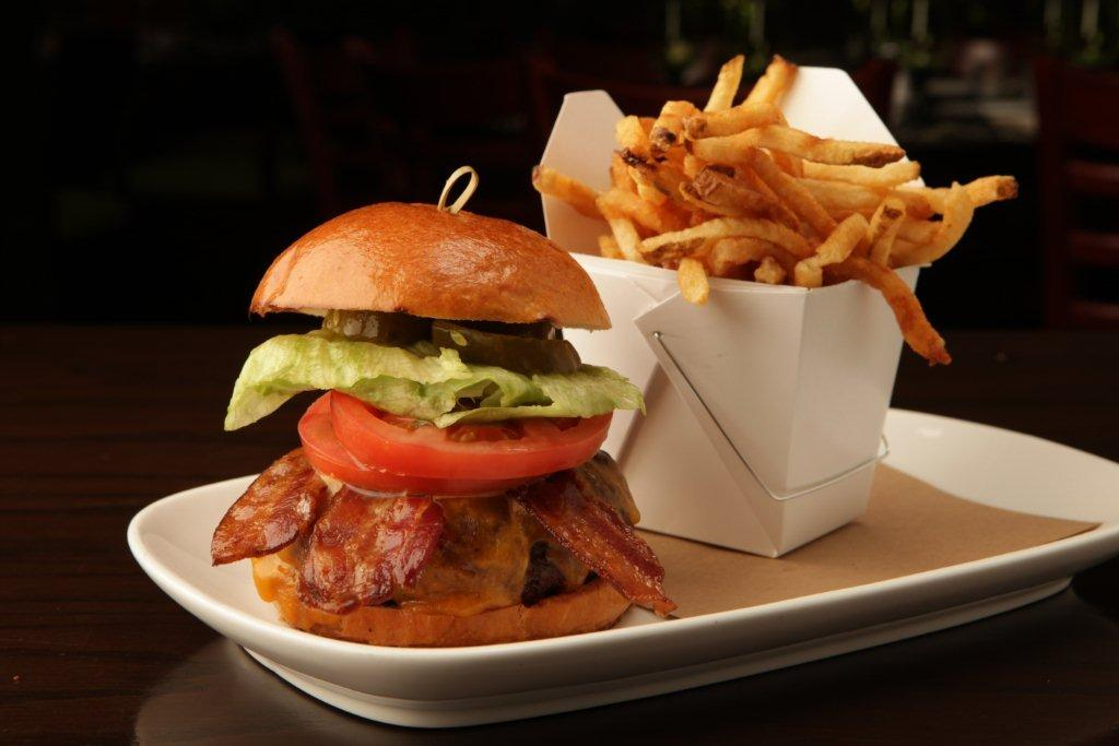 Prime Aged Angus Burger with bacon, lettuce, tomato, and pickles and french fries on the side.