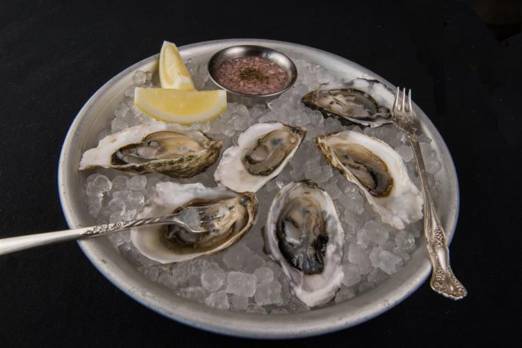 raw oysters on ice with side of dipping sauce and lemon wedges