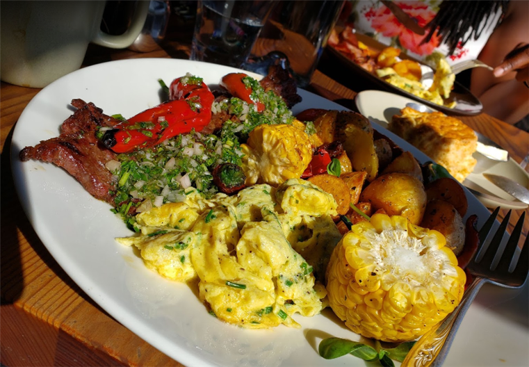 breakfast platter with scrambled eggs, potatoes, bacon, corn, and peppers