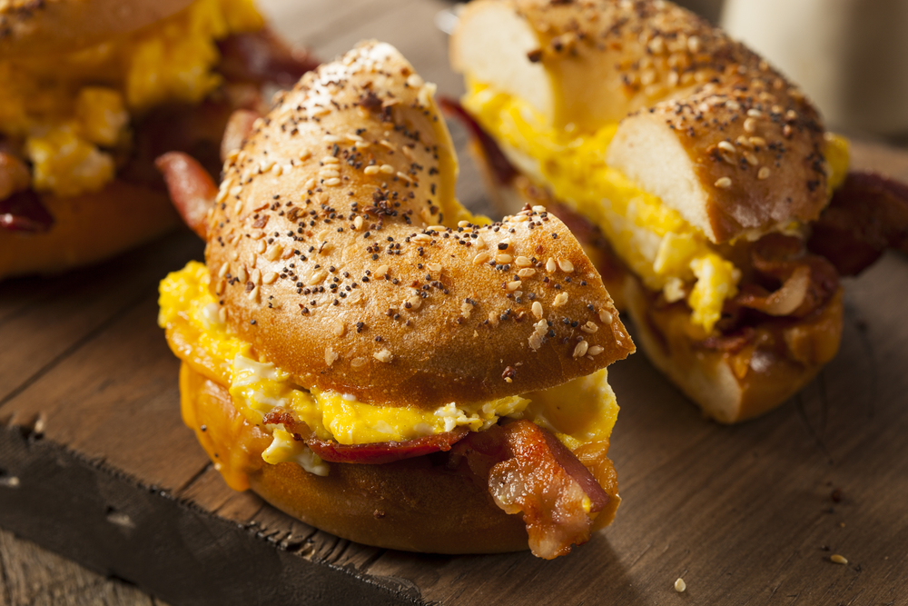 An everything bagel with egg, melted cheese, and bacon cut in half