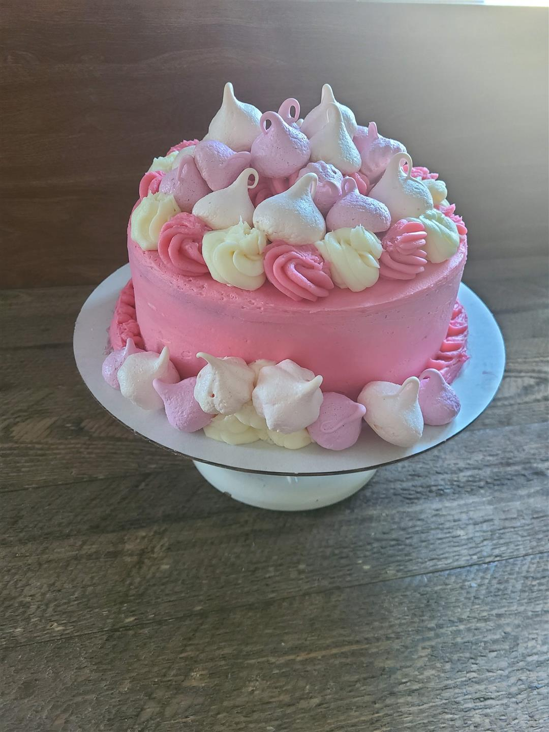 Circular cake with pink frosting and decorated with frosting swirls and meruinge