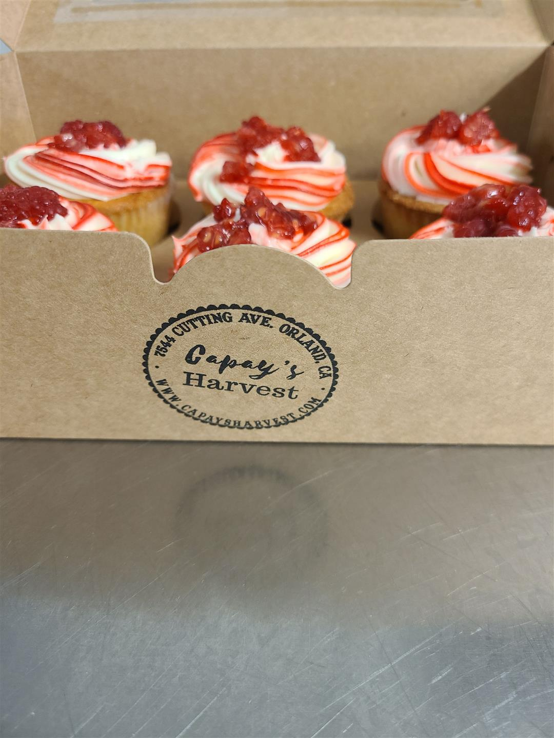Box of a half dozen cupcakes with white and red streaked rfosting and topped with a berry compote