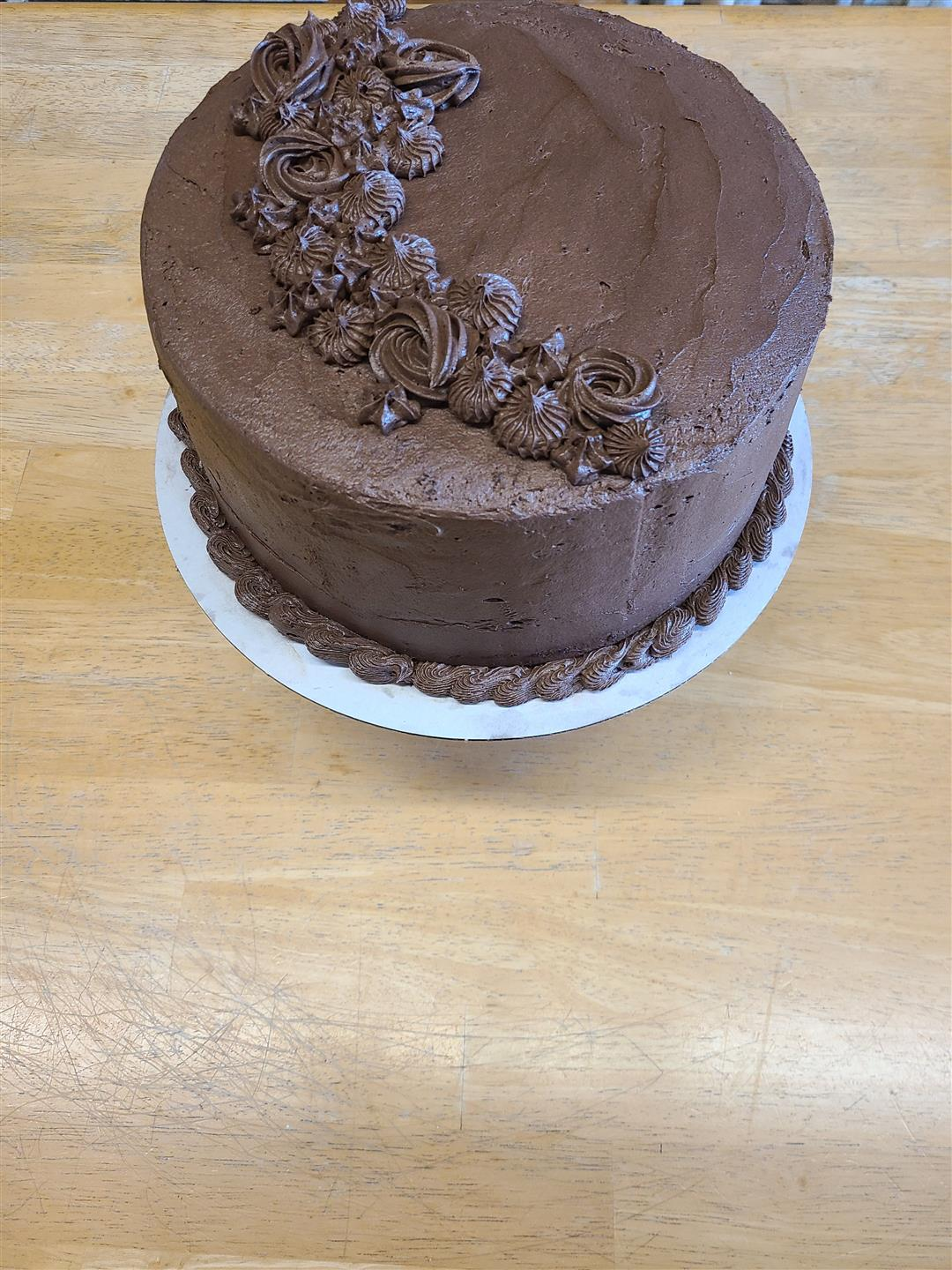 Chocolate frosted cake with piped design on top
