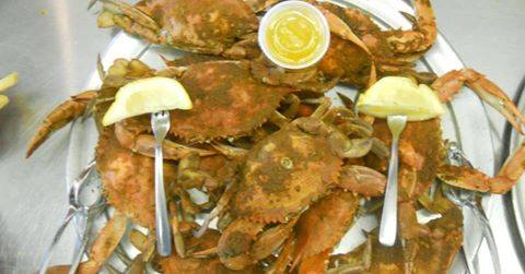 cooked crabs on a plate with lemon and butter sauce.
