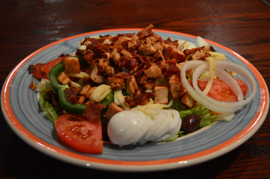 cobb salad with chicken, bacon, peppers and other toppings