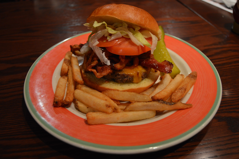 bacon cheeseburger with lettuce and tomato served with fries