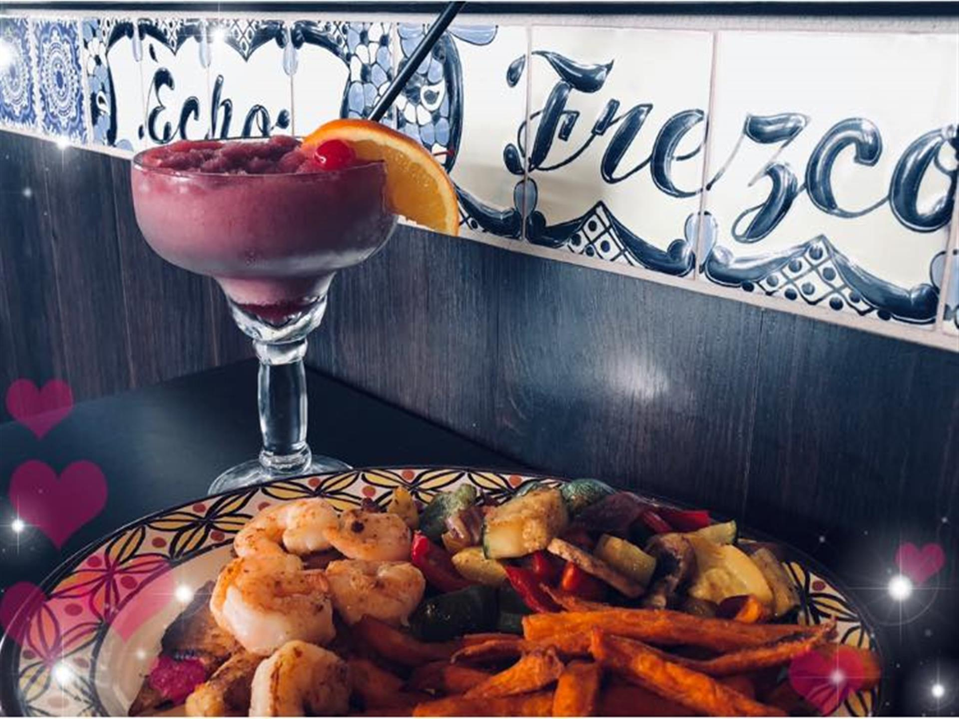 grilled steak topped with grilled shrimp. Sweet potato fries and vegetables on the side. Frozen cocktail with an orange slice and a cherry.