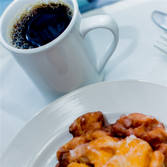 cup of coffee in a mug with an apple fritter on a plate